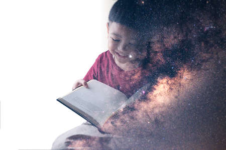 The double exposure image of the boy reading a book overlay with the milky way galaxy image. the concept of imagination, technology, future, and gaming.
