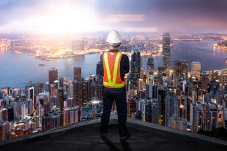 The double exposure image of the engineer standing back during sunrise overlay with cityscape image. The concept of engineering, construction, city life and future.