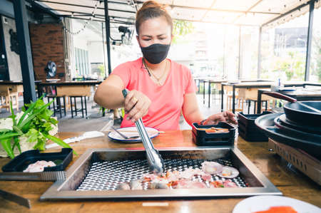the woman wearing the protective face mask and grilling in the restaurant via the new normal method. the concept of coronavirus, new normal, covid-19 and pandemic.