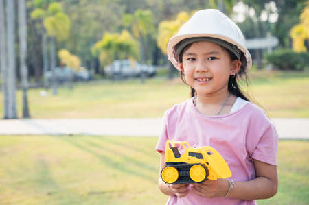 the little girl acting as are engineer in the park. the concpet of the education, intelligence playful and future.