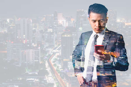the double exposure image of the businessman using a smartphone and overlay with cityscape image. the concept of 5G, smartphones, innovation and technology. Standard-Bild