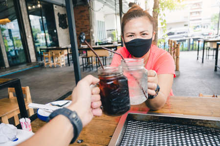 the woman wearing the protective face mask and celebrating with another one via the new normal method. the concept of coronavirus, new normal, covid-19 and pandemic. Imagens