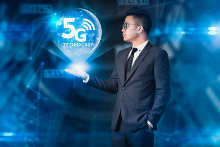 The businessman holding the 5G hologram . The concept of 5G, communication, technology and internet of things.