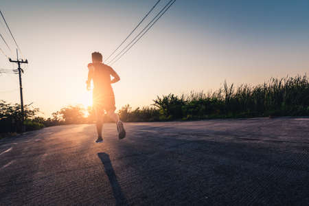 the man are running during the sunrise on the road. the concept of ennergy, activity, healthy, lifestyle and running. Standard-Bild