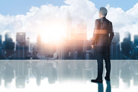 The double exposure image of the businessman standing on the rooftop  during sunrise overlay with cityscape image. The concept of modern life, business, opportunity  and future.