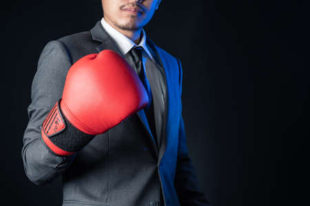 the businessman wearing a boxing mitts with the black copy-space. the concept of fighting, trade war, powerful and business.
