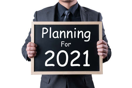 """the businessman holds a sign labeled """"planing for 2021�. the concept of new year, planing,strategy and business"""