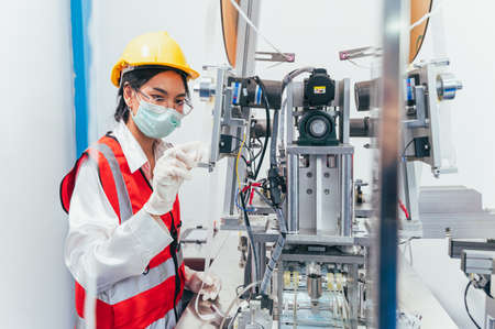 the manufacturing of the medical face mask in the factory via the machine. the concept of COVID-19, coronavirus pandemic, supply, healthcare and business. Standard-Bild