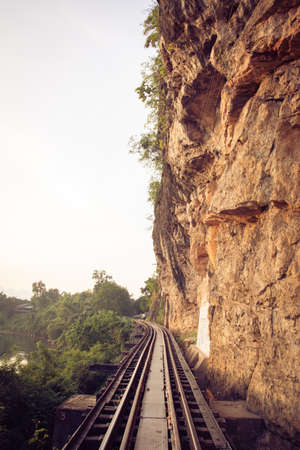 Railroad tracks through a forest, mountain and countryside, Thailand. photo