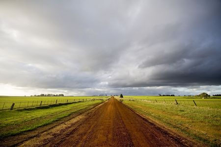 country: Verlaten land onverharde weg met donkere wolken en late winter licht.  Stockfoto