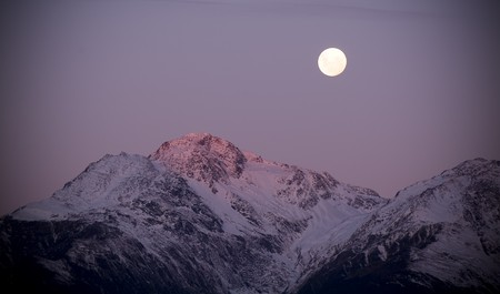 aspiring: Moon rises over snow capped mountains at twilight