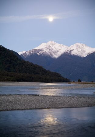 aspiring: Moon rises over snow capped mountains with river in foreground Stock Photo