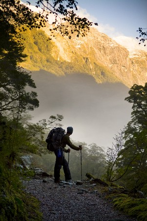A hiker pauses for a rest at a clearing while ascending into the mountains Stock Photo