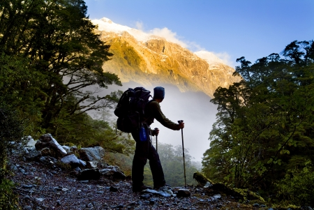 A hiker pauses for a rest at a clearing while ascending into the mountains photo
