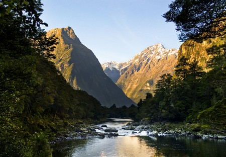 Spectacular mountain peaks and valley with river flowing through it.