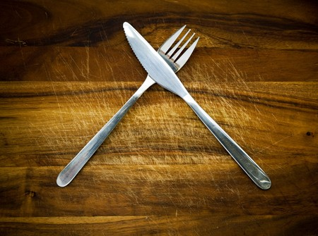 Stainless steel cutlery on a wooden chopping board Stock Photo - 7611793