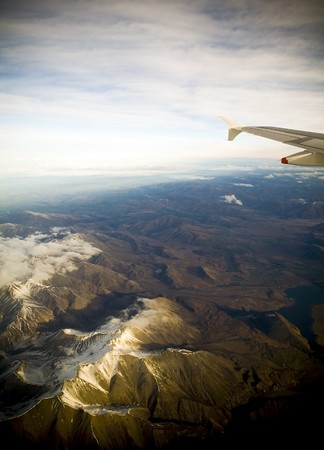 A passengers view of a planes wing high above the clouds and mountains photo