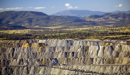 Huge walls of moved earth with roads through it in a large coal mine photo