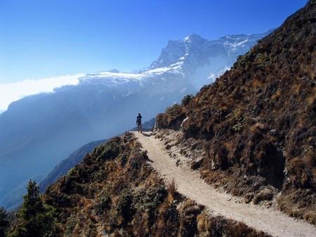 A lone trekker walks along a perfect mountain trail in the Himalaya, Nepal