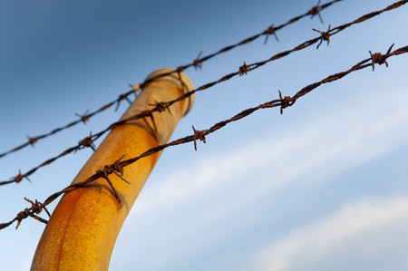 Fence posts with barbed wire running across it against a blue sky photo