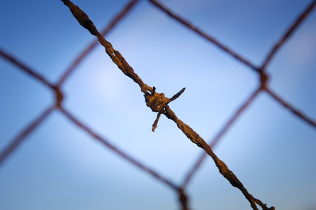 Close up of rusty, old barbed wire against a blue sky photo