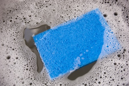 Blue sponge and dirty dish water in a sink photo