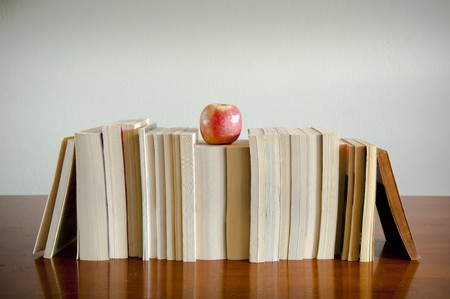 A row of books with an apple on top sits on a timber table with blank space behind photo
