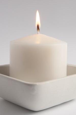 velas de navidad: Gran vela blanca en una bandeja cuadrada close up  Foto de archivo