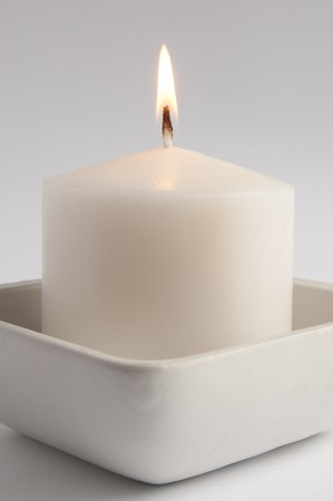 Large white candle in a square tray close up photo