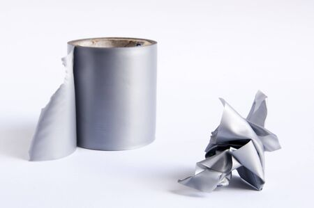 Roll of duct tape with torn off section in a rough ball photo
