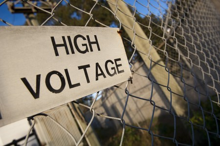 High voltage sign is aged on a wire (cyclone) fence photo