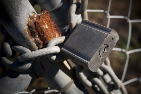 safekeeping: Large old padlock and chain on a wire gate Stock Photo