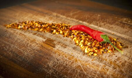 Red hot chilli concept - chilli sits atop chilli seeds shaped like a chilli photo