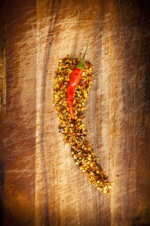 atop: Red hot chilli concept - chilli sits atop chilli seeds shaped like a chilli