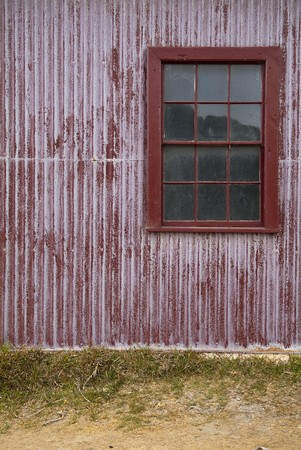 Red tin wall with a window and sandy ground photo