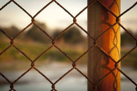 fencing wire: Rusty wire fence (cylcone fencing) in repeating patterns