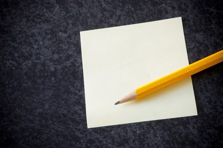 Yellow sticky note with a pencil against a dark marble background photo