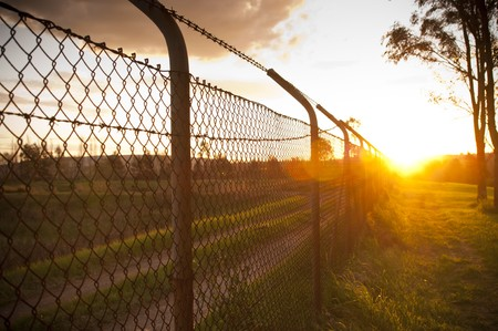 Old wire fence with the sun streaming alongside it photo