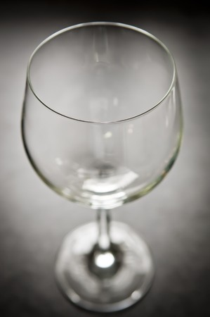 Large modern wine glass from above sits on bench top photo