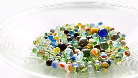 colourfully: Brightly colored marbles in different shades in a bright glass bowl