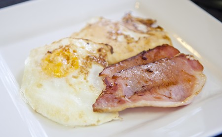 Homemade breakfast of bacon and eggs in white square plate photo