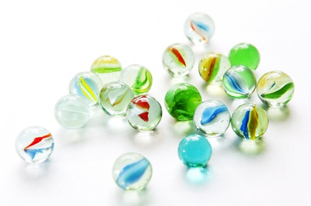 Brightly colored marbles in different shades on bright white photo