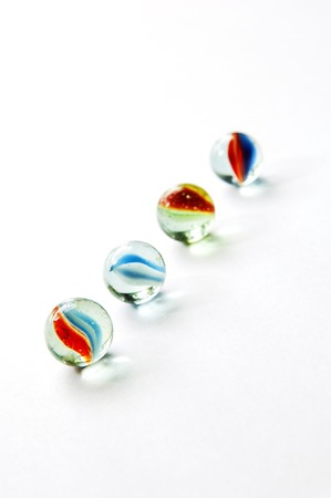 Brightly colored marbles in different shades on bright white Stock Photo
