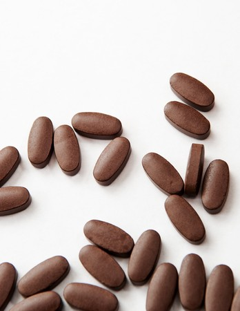 Generic brown pills spilled out over white photo