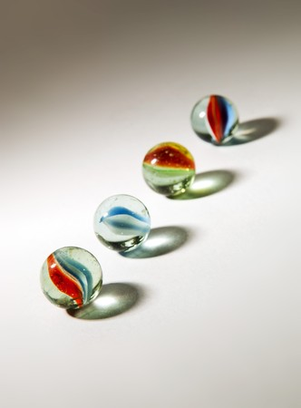Brightly colored marbles in different shades with deliberately long shadows photo