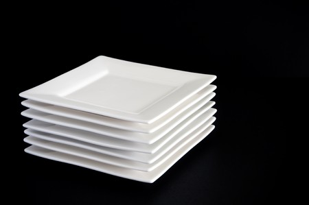 black dish: Contemporary square white plates stacked against a dark black background Stock Photo