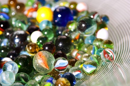 Brightly colored marbles in different shades in a bright glass bowl photo