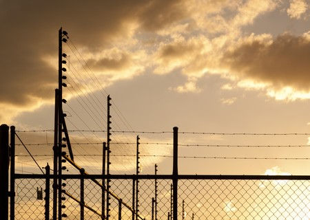 Large fences and barbed wire against a sunset sky with copy space Stock Photo - 8235058