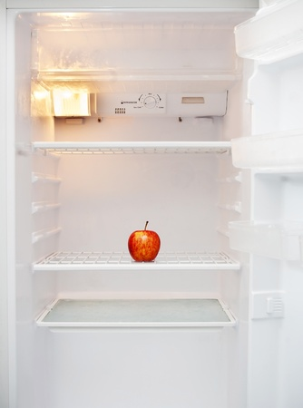 An white fridge with only a single apple inside it photo