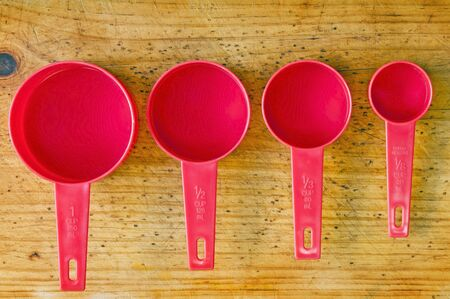 Red measuring cups in different sizes on a timber board Stock Photo - 8437711